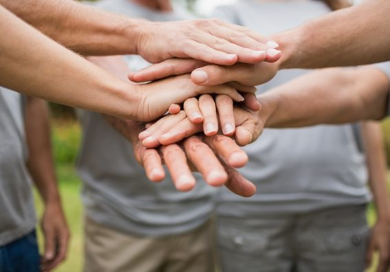 hands stacked together to volunteer